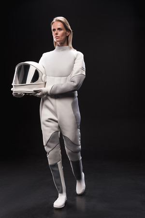 Full-length of young spacewoman wearing protective costume is going ahead and looking aside wistfully while holding her helmet. Isolated background. Cosmos concept Фото со стока