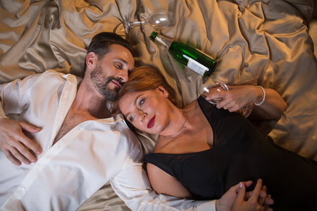 Top view of happy married couple lying on bed with relaxation and holding hands. Glasses and bottle of champagne on beddings