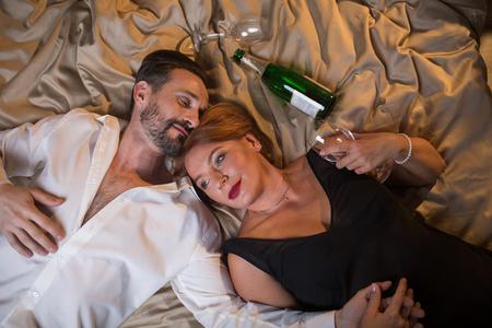Vue de dessus de l'heureux couple marié allongé sur le lit avec détente et main dans la main. Verres et bouteille de champagne sur la literie Banque d'images - 91858141