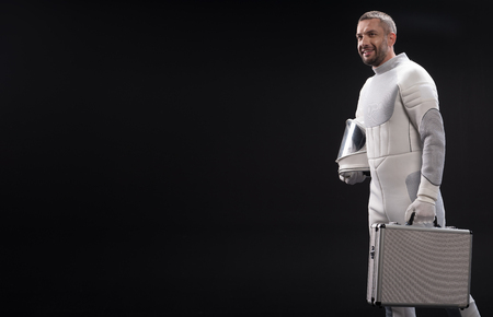 Optimistic bristled spaceman in protective costume is acting as businessman while holding diplomat and helmet. He is looking ahead with bright smile. Isolated and copy space. Business in space concept Stock Photo