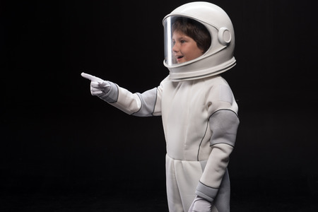Look here. Side view of surprised cute small cosmonaut is standing in helmet and specialized protective suit and pointing finger while looking aside with curiosity and smile. Isolated background Фото со стока