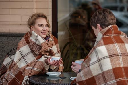 居心地の良いリラックス。お互いを見つめ合いながら、熱い飲み物を飲みながらカフェに座っている男女の肖像画をウエストアップ。柔らかい毛布