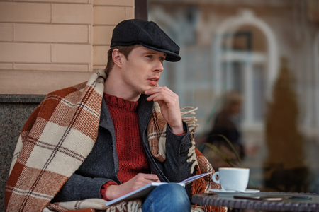 Waist up portrait of pensive male sitting in chair with blanket and espresso. He is holding notebook and pencil while thinking