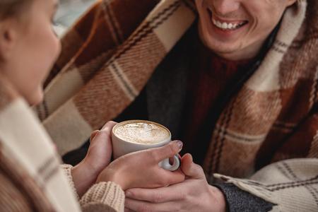 笑顔の男女の手にコーヒーのマグカップをクローズアップ。テーブルに座っている間、毛布で覆われている。 写真素材