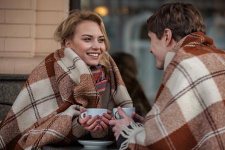 熱い飲み物を楽しみながら柔らかい毛布で覆われた男女の肖像画をウエストアップ。彼らは愛とケアを表現するお互いを見ている