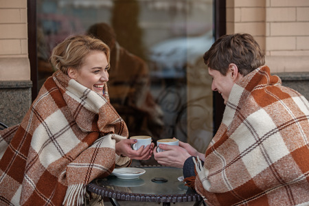 Charming couple sitting at table and holding mugs of hot drink. Girl is laughing while and looking at boy while he is smiling with closed eyes