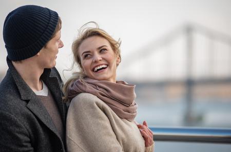 Echte emoties. Taille op portret van mooie man en vrouw die elkaar bekijken terwijl status in openlucht dichtbij rivier met brug op achtergrond. Kopieer de ruimte aan de rechterkant Stockfoto