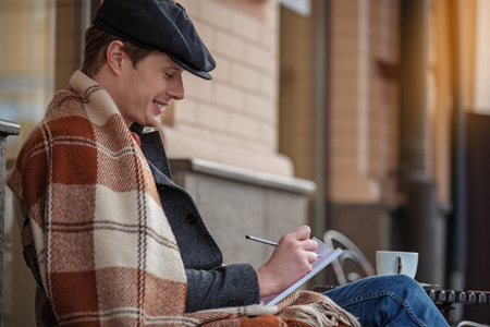 Side view of charming male with blanket relaxing with notebook and tea. Copy space in right side