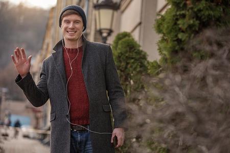 Portrait en demi-longueur d'un charmant homme marchant dans la ville avec téléphone et casque. Il exprime l'ouverture et la convivialité Banque d'images - 92058419