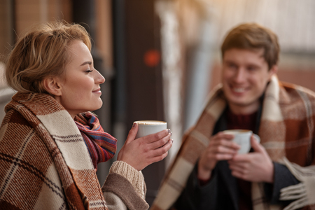Amorous couple sitting outdoors with cozy blankets. Focus on lady smelling aroma of hot coffee while boy is looking at her with tenderness Imagens
