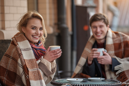 Waist up portrait of young man and woman relaxing at cafe with latte. Focus on lady laughing and looking at camera Stock Photo