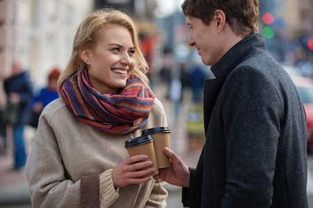 Charming man and woman holding coffee while standing in the street. They are looking at each other expressing love and tenderness