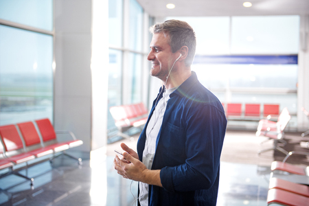 Favorite melody. Side view profile of happy adult man is listening to music through earphones using mobile phone. He is standing at airport lounge and expressing gladness