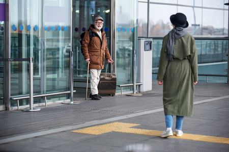 Full length of senior man is exiting from airport building while carrying suitcase. He is expressing gladness while seeing stylish woman who is waiting for him. Back view of lady