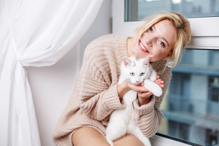 Portrait of kind lady sitting on sill and holding cat with big sweetness. She is looking at camera and smiling