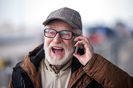 Pleasant conversation. Cheerful bearded aged man with glasses is enjoying phone communication while is standing outdoors and looking aside with happiness
