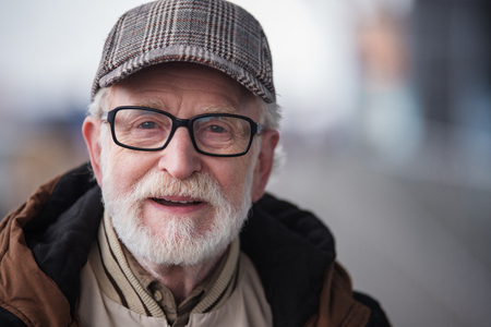 Good day. Close-up portrait of cheerful gray-haired bearded gentleman in glasses is standing outdoors. He is looking at camera with joy. Copy space in the right side
