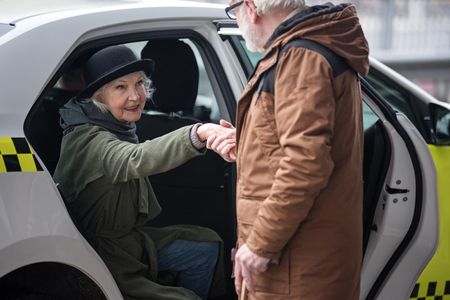 You are so kind. Old man is helping elegant senior woman to get out of taxi. She is looking at him gratefully. Focus on female Stock Photo