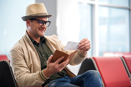 Checking details. Joyful middle-aged man in hat is looking at ticket with smile while sitting on bench at airport lounge. He is waiting for his flight. Copy space in the right side