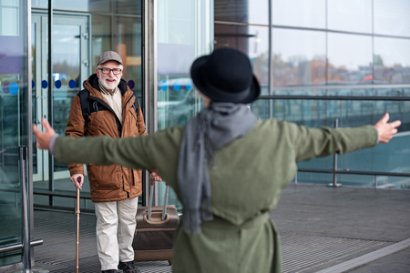 After long separation. Back view of elegant senior woman is going to hug her smiling gray-haired husband who is exiting from airport building. Focus on man with suitcase Stock Photo