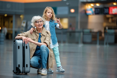 My best friend. Full length portrait of trendy optimistic senior grandmother is squatting and resting on suitcase in airport while her grandchild is hugging her for shoulders. Copy space in right side