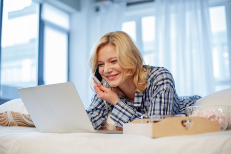 Portrait of glad lady enjoying communication at home. She is looking at laptop screen and smiling. Tray with breakfast is on bed