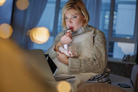 ノートパソコンでビデオを見て哀れな顔を持つ女性の肖像画。彼女は座ってマシュマロを食べている。左側の領域をコピーする