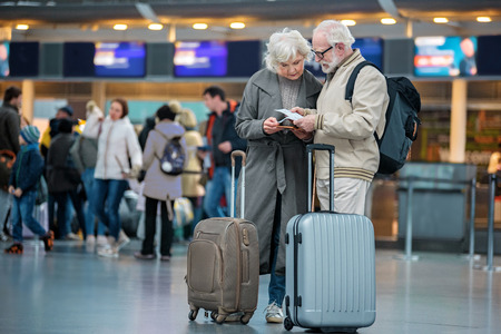 Checking trip details. Full length of serious senior wife and husband are standing with suitcases at international airport and looking at flight tickets with concentration. Copy space in left side Stock Photo - 92226686