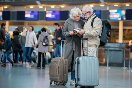 Verificando os detalhes da viagem. O comprimento cheio da esposa e do marido sênior sérios está estando com as malas de viagem no aeroporto internacional e está olhando bilhetes do vôo com concentração. Copie o espaço no lado esquerdo