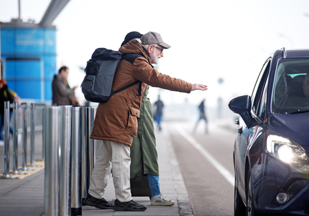 Need transport. Full length side view of senior couple is standing near road. Profile of positive bearded old man in glasses and with backpack is raising hand while stopping car Stock Photo