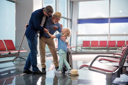 家族は抱きつきます。白髪の祖父と小さな女の子を持つ肯定的な成熟した父親の完全な長さは、空港のラウンジに立って、抱擁しています。彼らは幸せを表現している。右側にスペースをコピーする 写真素材 - 92226824