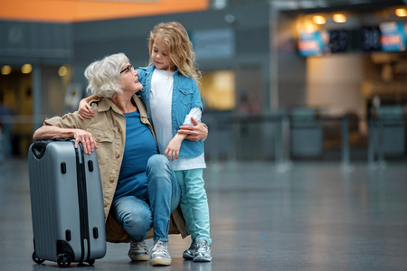 Full length of happy elegant gray-haired grandmother is squatting and resting on suitcase in waiting hall while hugging her small grandchild. They are looking at each other with smile. Copy space Banco de Imagens - 92227039