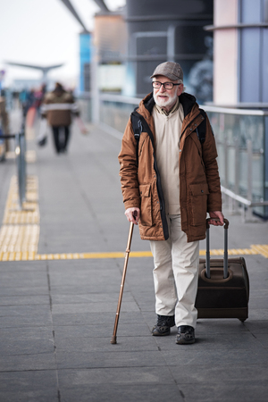 Finally homeland. Full length portrait of aged man with cane is walking along the airport building and carrying suitcase. He is looking aside thoughtfully. Copy space on left side