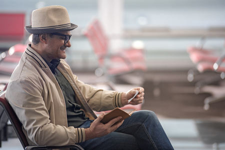 Side view profile of delighted adult male tourist is looking at boarding pass with smile while sitting on red seat at airport lounge. He is waiting for his flight. Copy space in the right side Stock Photo