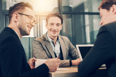Portrait of happy businessman speaking with comrades while situating at desk in office. Communication and profession concept