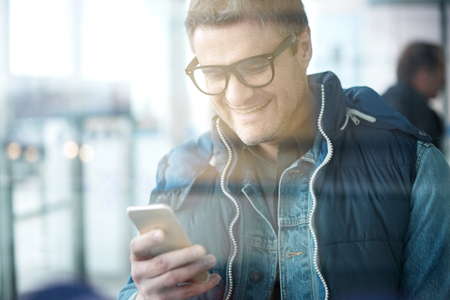 Always in touch. Happy adult bristled man in glasses is looking at screen of his mobile phone and sharing pleasant news. He is standing at international airport. View through the glass Stock Photo