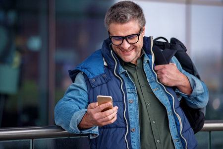 Funny message. Positive middle-aged man with backpack is sharing news using mobile phone. He is looking at screen with smile while leaning on railing near airport building Stock Photo