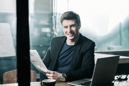 Portrait of cheerful young man reading newspaper during break at table in office. Relax and occupation concept Zdjęcie Seryjne