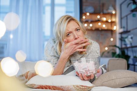 マシュマロをたくさん食べようとする若い女性の肖像画。ガーランドは後ろにいる左側の領域をコピーする