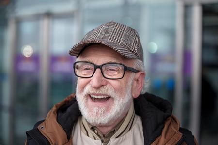Nur positive Emotionen . Close-up Portrait von erfreut bärtiger alten Mann in Gläsern steht im Freien und lachen Standard-Bild