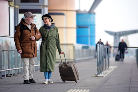 Enjoy your life. Full length of encouraged calm retired man and woman are talking to each other while standing outdoors. They are carrying suitcase while looking at each other with love. Copy space