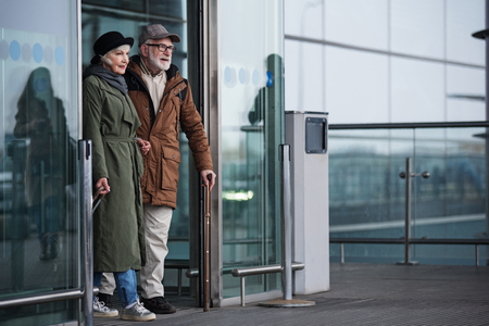 Finally at home. Full length of positive elegant old man and woman are going out of doors from terminal. Male is exiting with cane while female is carrying her suitcase. Copy space in the right side Stock Photo