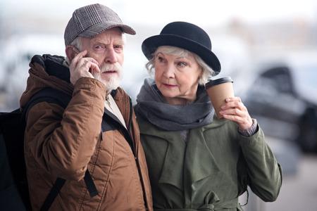 Toujours en contact. La taille d'un homme sérieux regarde la caméra pensivement tout en ayant une conversation désagréable. Il est debout avec une charmante dame âgée qui boit un expresso et le regarde Banque d'images - 92227276