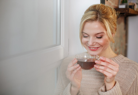 Portrait of smiling woman drinking tasty tea in the morning. Copy space in left side Stock Photo