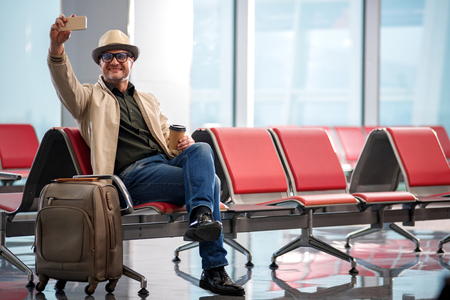 Shoot for remember. Full length portrait of delighted mature man in hat is sitting on red chair at airport lounge. He is taking selfie with help of smartphone while drinking fresh coffee. Copy space 版權商用圖片