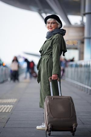 여행 준비. 긍정적 인 수석 여자 모자를 착용의 전체 길이는 기쁨을 함께 카메라를 찾고있는 동안 야외 가방에 서있다. 그녀는 국제 공항에있다.