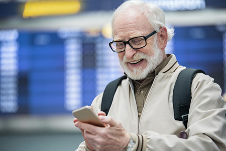 Smart gadget. Joyful gray-haired man in glasses is looking at screen of his mobile phone and expressing gladness. He is standing at airport against electronic timetable. Copy space in the left side Stock Photo
