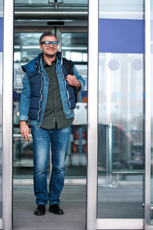 Feeling wonderful. Full length portrait of positive bristled man with backpack is exiting from international airport. He is looking ahead with smile