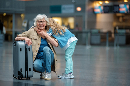 Full length portrait of stylish positive old grandmother is squatting and resting on suitcase in waiting hall while her small grandchild is hiding head and hugging her for shoulders. Copy space