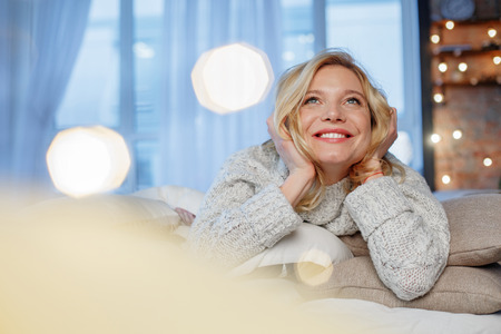 Low angle portrait of positive girl enjoying comfort in apartment. She is looking up. Copy space in left side Stock fotó